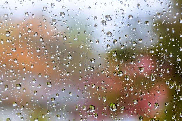 Krople deszczu na niebieskim tle szkła. uliczne bokeh światła z ostrości.