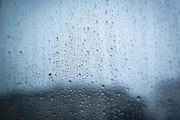 Krople deszczu na oknie, deszczowa pogoda, pochmurny dzień. selektywna ostrość, tło niewyraźne krawędzie