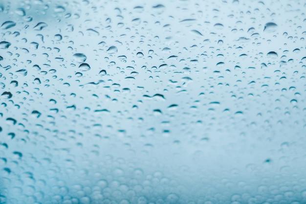Krople deszczu na oknie. kropelki wody na szkle. niebieski odcień