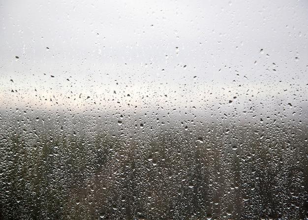 Krople deszczu na oknie z abstrakcyjnym tle przyrody nieostry