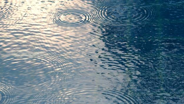 Krople deszczu na powierzchni niebieskiej wody w basenie, które mają wpływ falowania na teksturę cieczy i kąt widzenia z góry.