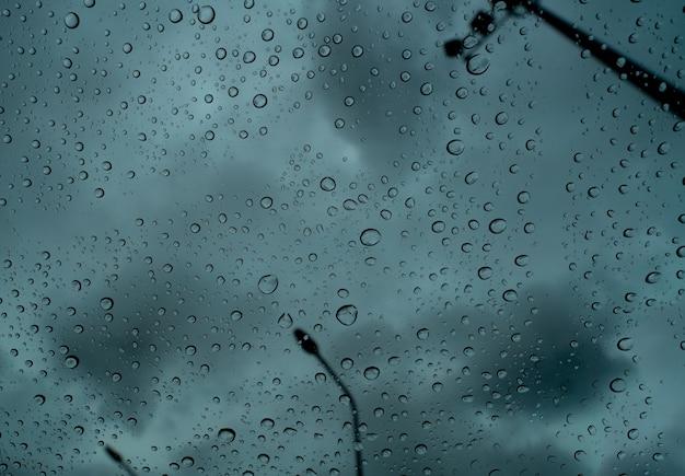 Krople deszczu na przezroczystym szkle na tle ciemnego burzowego nieba i słupa elektrycznego.