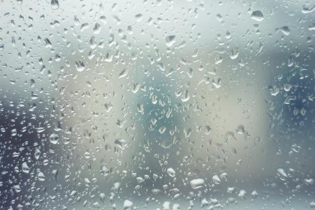 Krople deszczu na szkle z niebieskim odcieniem