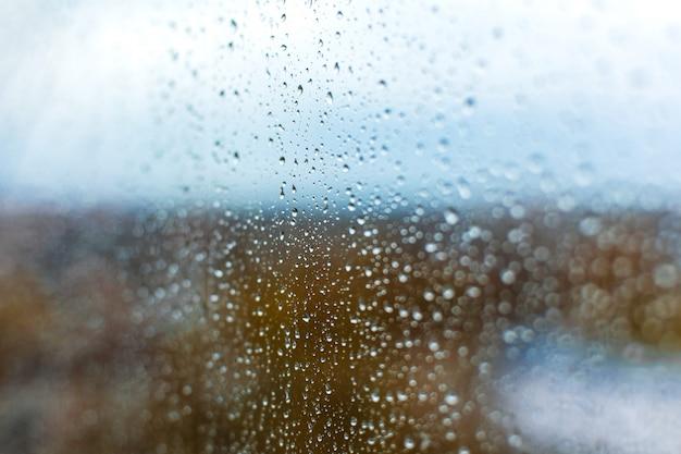 Krople deszczu na szybie na tle jesiennego miasta