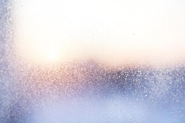 Krople deszczu na szybie okiennej na deszcz, zachód słońca.