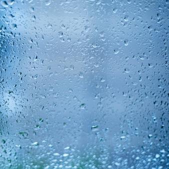 Krople deszczu na szybie okna. płytkie dof. okno po deszczu. błękitne wody tło z wodnymi kroplami.