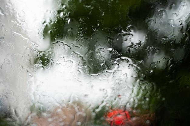 Krople deszczu na szybie przedniej z niewyraźnymi nocnymi światłami miasta w tle.