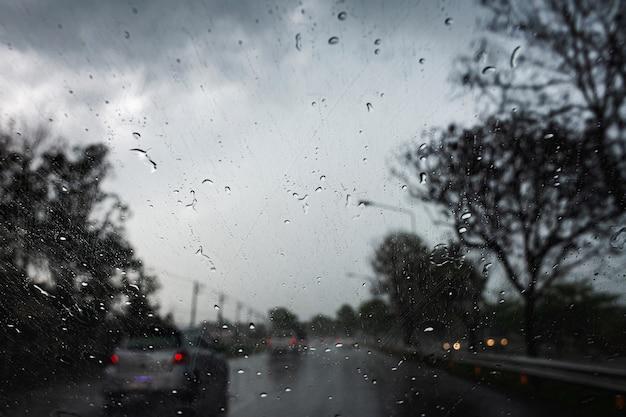 Krople deszczu na szybie samochodu podczas jazdy przez ulewne deszcze i fale sztormowe.