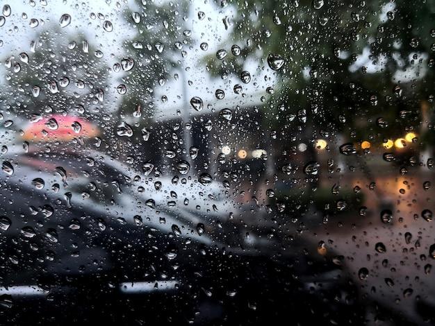 Krople deszczu na szybie samochodu z rozmytym tłem.