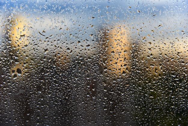 Krople deszczu na zbliżeniu szyby okna i niewyraźne widmowy pejzaż miejski.