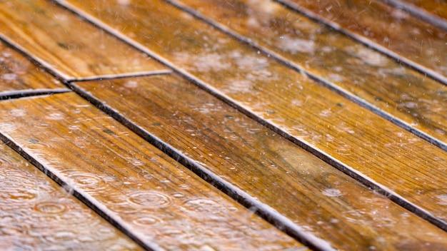 Krople deszczu spadają na drewniany taras i most przy basenie z bliska