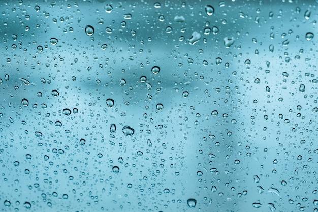 Krople deszczu, woda spada na szkło wiosną. abstrakcyjne tło