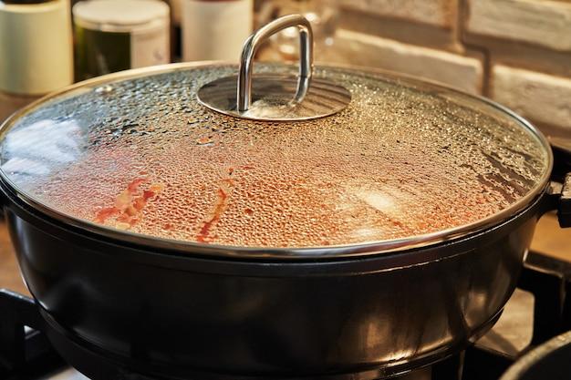 Krople na szklanej pokrywie patelni przygotowującej danie w piekarniku z selektywnym skupieniem.