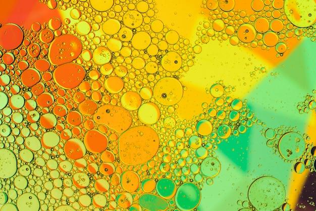 Krople oleju w wodzie na kolorowym tle