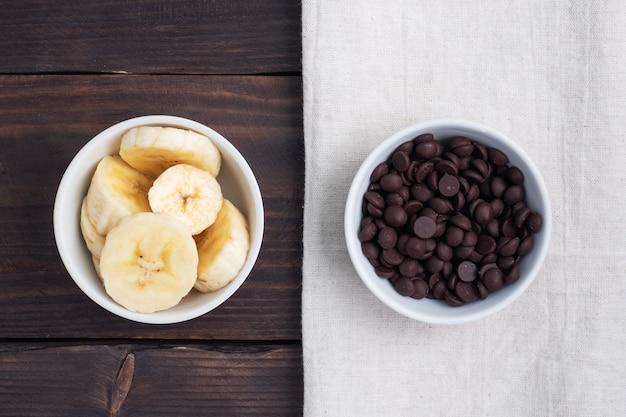 Krople pokrojonego banana i czekolady w talerzu. składniki na deser, koncepcja