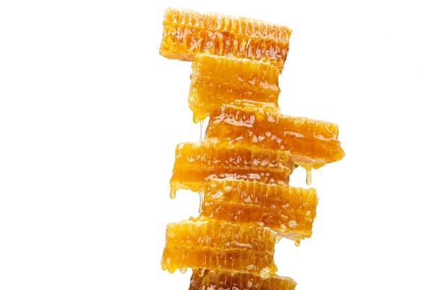 Krople świeżego miodu kapiące z piramidy woskowego miodu