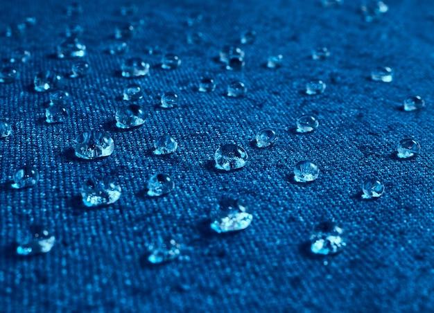 Krople wody deszczowej na niebieskim wodoodpornym materiale.