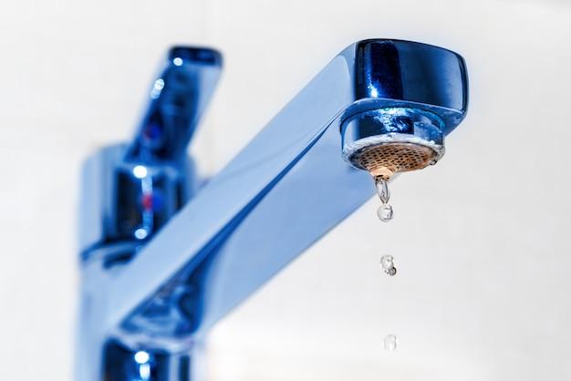 Krople wody kapią z chromowanej baterii w zlewie kuchennym lub łazience. pojęcie idei oszczędzania wody.