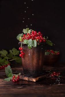 Krople wody leje się na dojrzałe jagody czerwonej porzeczki w glinianej misce na ciemnym drewnianym stole, w stylu rustykalnym, z bliska.