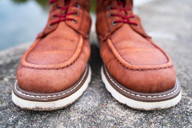 Krople wody na czerwonych skórzanych butach roboczych
