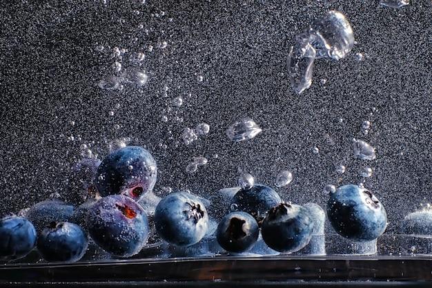 Krople wody na dojrzałej słodkiej jagodzie. świeże jagody tło z miejsca kopiowania tekstu. koncepcja wegańska i wegetariańska. makro tekstury jagód borówki.