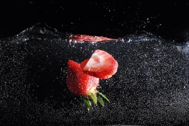 Krople wody na dojrzałej słodkiej truskawce. świeże jagody tło z miejsca kopiowania tekstu. koncepcja żywności wegańskiej.