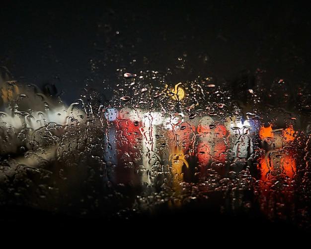 Krople wody na oknie rozmywają czarne światła na zewnątrz
