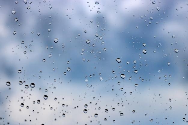 Krople wody na powierzchni szkła na niebieskim tle