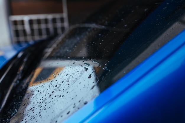 Krople wody na przednią szybę samochodu. koncepcja myjni samochodowej