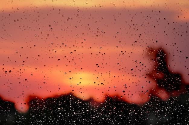Krople wody na szybie na niewyraźne tło nieba i drzew podczas wschodu słońca