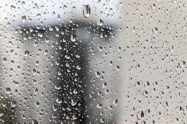 Krople wody na szybie okna na niewyraźnym tle w pochmurny, deszczowy dzień