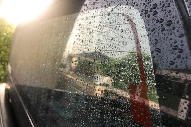 Krople wody na szybie samochodu z miękkim światłem