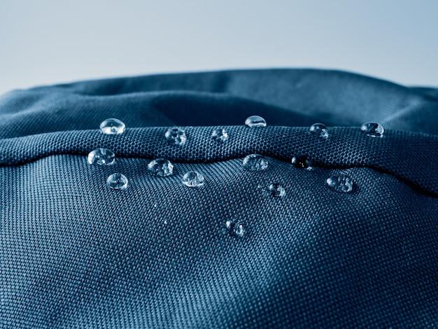 Krople wody na wodoodpornej tkaninie membranowej. widok szczegółów tekstury niebieskiej tkaniny wodoodpornej.