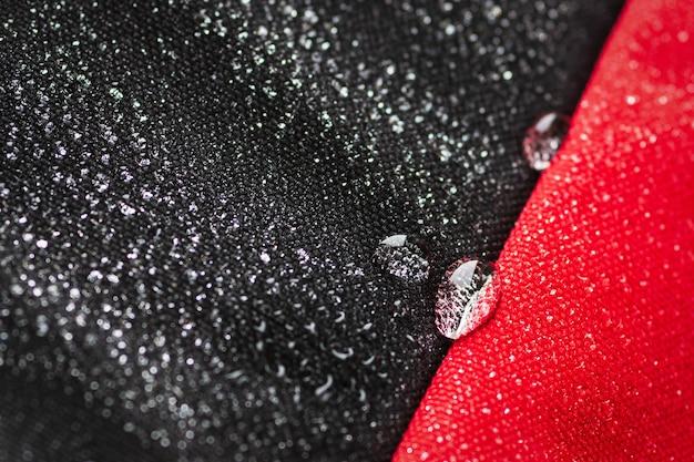 Krople wody na wodoodpornej tkaninie wodoodpornego worka z czarnego i czerwonego materiału