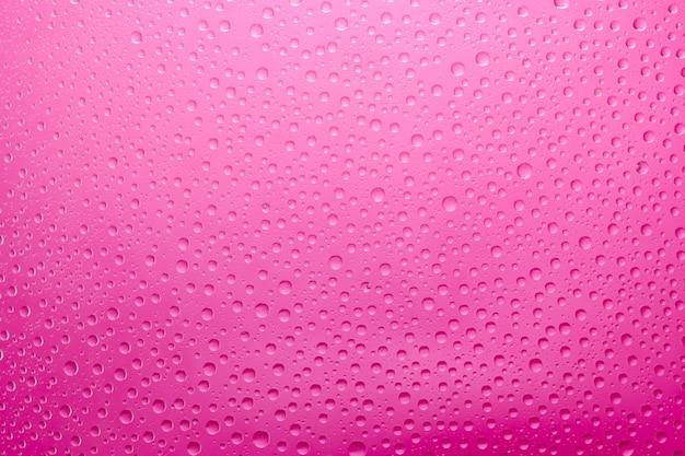 Krople wody różowe tło. krople wody na tle szkła