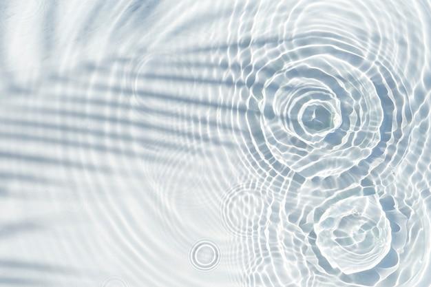Krople wody spadają na przezroczystą taflę wody i cień liścia palmy. widok z góry, układ płaski.