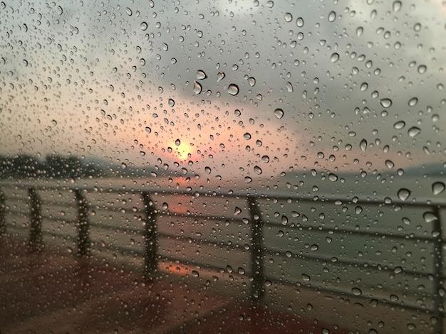 Krople wody zroszony na szklane okno w zachodzie słońca.