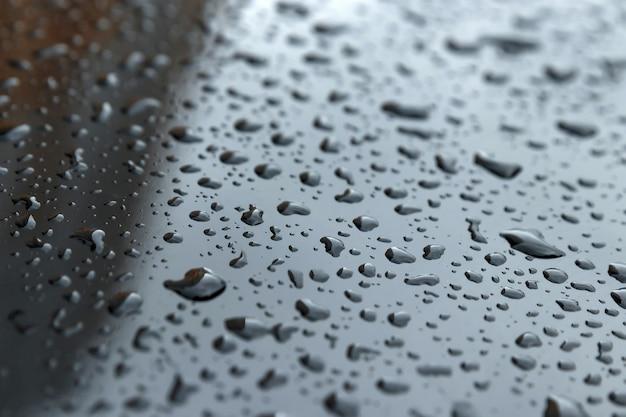 Krople z bliska na ciemnym kapturze. koncepcja deszczu, kondensacji