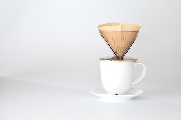 Kroplowy kubek kawy świeżo gorący na papierowym filtrze