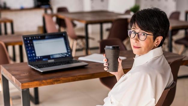 Krótka z włosami biznesowa kobieta z kawą i laptopem