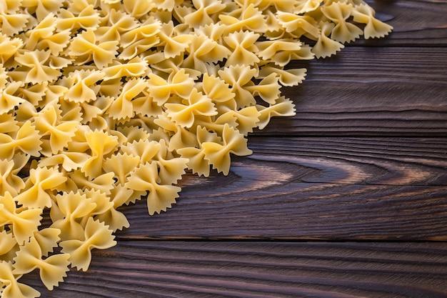 Krótki makaron farfalle na ciemnym tle drewna. surowy żółty makaron. kuchnia włoska. skopiuj miejsce
