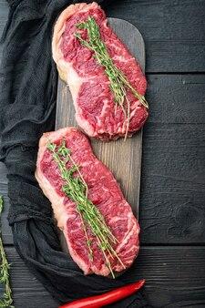Krótki surowy stek wołowy z polędwicy wołowej, na czarnym drewnianym tle, widok z góry, z kopią miejsca na tekst
