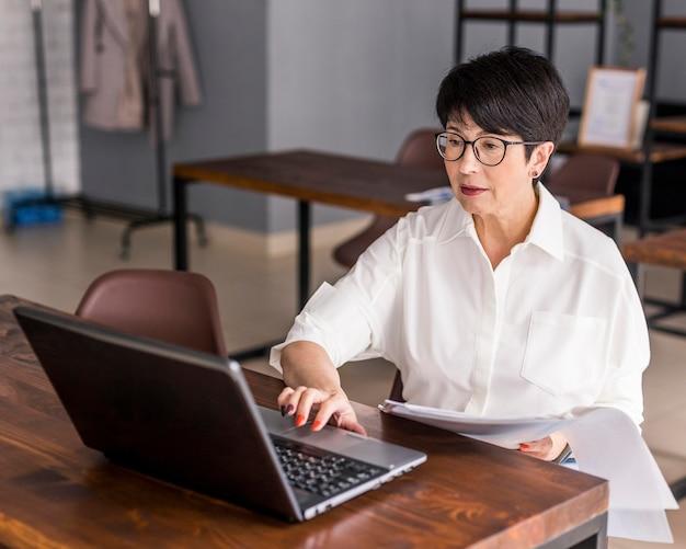 Krótki z włosami biznes kobieta pracuje na laptopie