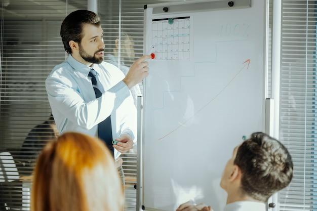 Krótkie terminy. przystojny młody szef stojący obok tablicy i wskazujący na przypięty do niej kalendarz, rozmawiając o terminach realizacji projektu