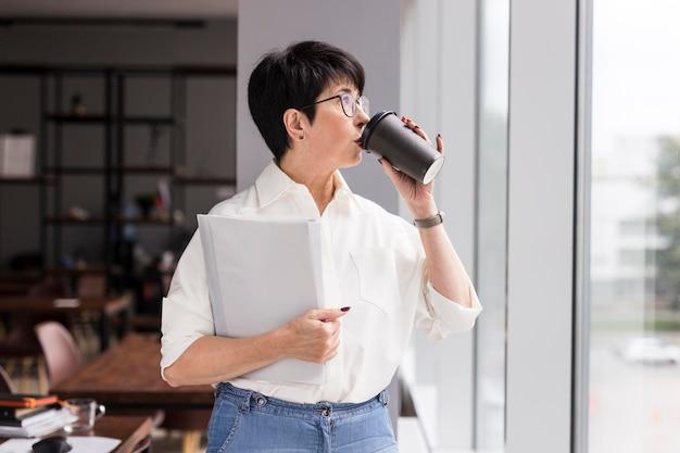 Krótkie włosy biznes kobieta picia kawy z ukosa