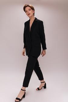 Krótkie włosy pani w ciemnym garniturze na białym tle. urocza kobieta w czarnych pasach i oversize'owej kurtce spaceruje po odosobnionym