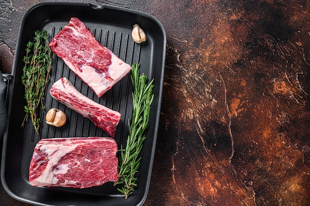 Krótkie żeberka wołowe mięso na patelni grillowej gotowe do gotowania. ciemne tło. widok z góry. skopiuj miejsce.