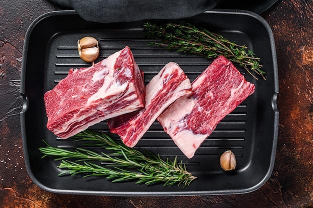 Krótkie żeberka wołowe mięso na patelni grillowej gotowe do gotowania. ciemne tło. widok z góry.