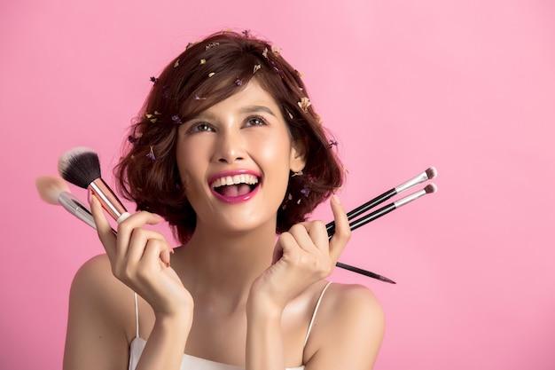 Krótkiego włosy azjatykcia młoda piękna kobieta stosuje kosmetyka proszka muśnięcie