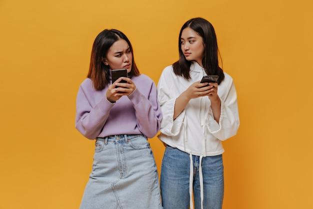 Krótkowłosa azjatka w dżinsowej spódnicy i fioletowym swetrze patrzy na swoją przyjaciółkę z podejrzliwością. brunetka kobieta w białej bluzie z kapturem pozuje na pomarańczowej ścianie